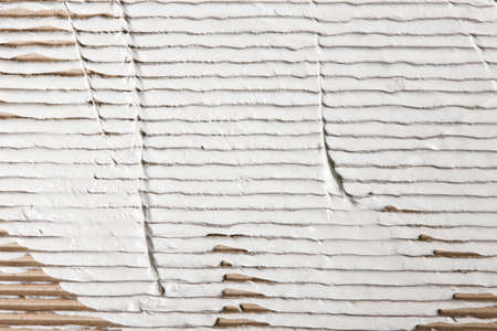 careless: White stucco smeared on beige corrugated cardboard, closeup. Repair background with free space for text.