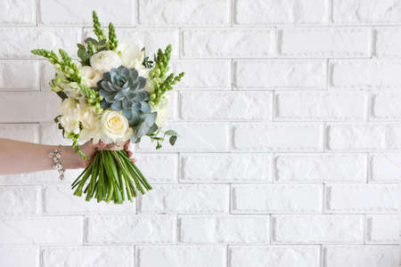 Female hand gives bunch with roses and succulent on white brick background. Gift for mother or woman, florist work, wedding decor, beautiful bouquet sale concept Stock Photo