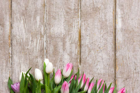 Frame of pink tulips on wooden background. Flower bouquet in florist workplace with copyspace. Wedding, gift, birthday, 8 march, mothers day greeting card concept Stock Photo
