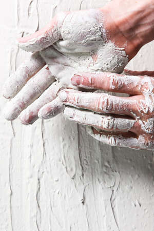 gyps: Worker hands in white stucco background, flat lay. Repair, construction work, building, plastering concept