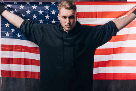 Young USA patriot holds national flag. Strong man in black cloth with stars and stripes behind him. Independence day, confidence, pride, fidelity to the nation, memorial day concept