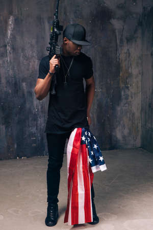 Afro american man in black cloth with flag and weapon stay on dark background. Gangster, patriotism, social problem, immigration, us citizenship, armed strike, bandit groups concept