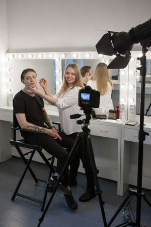 Vertical indoors shot of beautician putting makeup to man and looking at camera while smiling. Recording video for visage blog. Male beauty concept. Stock Photo