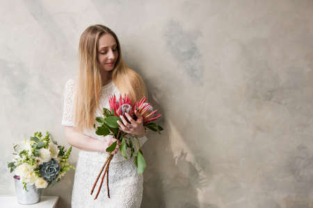 Woman with bouquet of protea king flower on wall background. Beautiful girls gift, bouquets delivery, floristic shop concept