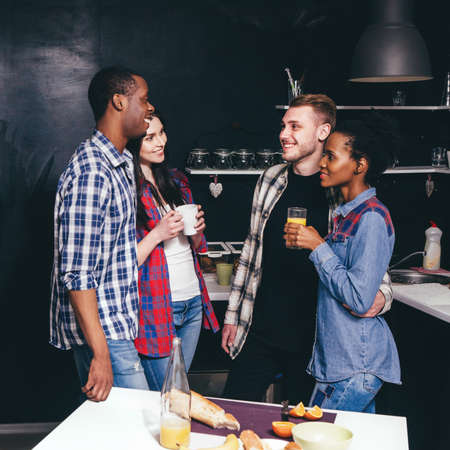 Company of friends in kitchen together. Two happy couples have fun, talking and smiling. Interracial relationship, support, neighbors, friendship and togetherness concept. Stock Photo