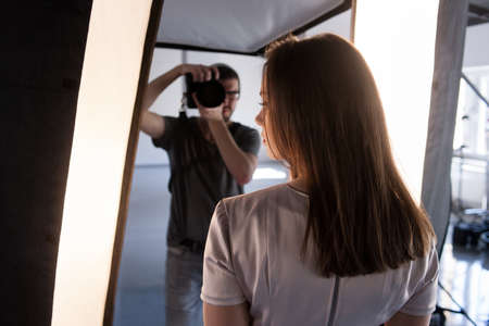 Photo session backstage. Photographer shoot model. Back view from womans shoulder on studio interior and man, who work with camera