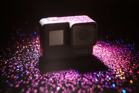 Kharkov, Ukraine - April 13, 2017: GoPro HERO 5 digital action camera in backlight with sparkles on black. Compact gadget waterproof , support 4k video and is often used in extreme photography