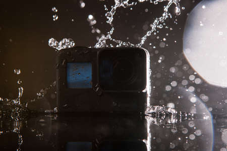 Kharkov, Ukraine - April 13, 2017: GoPro HERO 5 digital action camera with water drops with lensflare on black. Compact gadget waterproof , support 4k video and is often used in extreme photography Editorial