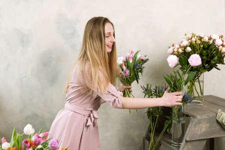 Florist choose flower for bouquet. Decorator workshop. Woman in flower shop workplace , assembling spring pink composition Stock Photo