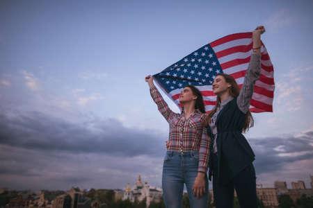 spolužák: Americké dospívající s vlajkou cestování po celém světě. Šťastné dívky na střeše. Teenager sestry na dovolené slaví den nezávislosti na pozadí oblohy Reklamní fotografie