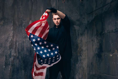 Young USA patriot with flying american flag. Strong man in black cloth on dark studio background. Independence day, confidence, pride, fidelity to the nation, memorial day concept