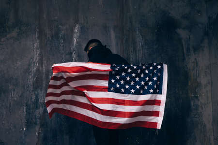 Flying USA flag and unrecognizable man. Back of guy in black cloth on dark studio background. Independence day, confidence, pride, fidelity to the nation, memorial day concept Фото со стока