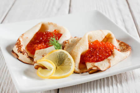 hotcakes: Dessert pancakes with red caviar on white plate. Russian traditional salty crepes with seafood. Shrove tuesday holiday food