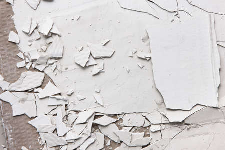 gyps: Pieces of white cracked plaster, closeup. Old peel wall background with free space. Repair and construction. Error in the technology of application of building materials Stock Photo