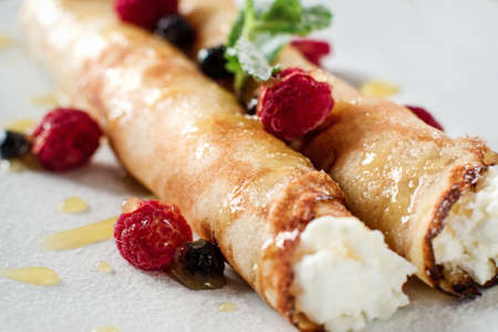 poured: Sweet crepe with cottage cheese and berriesm closeup. Restaurant serving of healthy morning breakfast. Homemade rolled pancake dessert with raspberries on white plate.