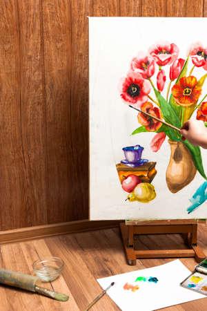 unrecognizable: Professional painter drawing watercolor flowers. Unrecognizable artists hand paints bouquet picture . Drawing lessons, art school, young artist concept