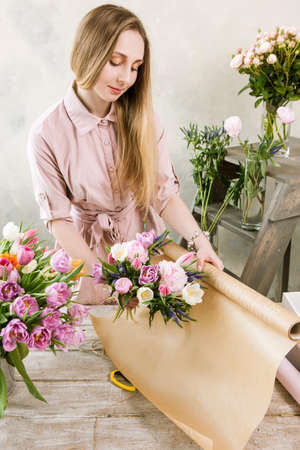 warehouse: Woman packing pink spring bouquet top view. Young florist make floristry assemble in workshop on wooden background
