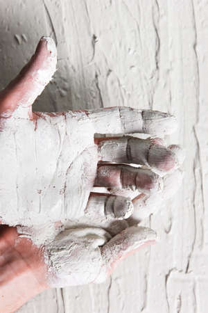 negligent: Plastering work, building. Dirty worker hands in white stucco on rough background, flat lay. Stock Photo