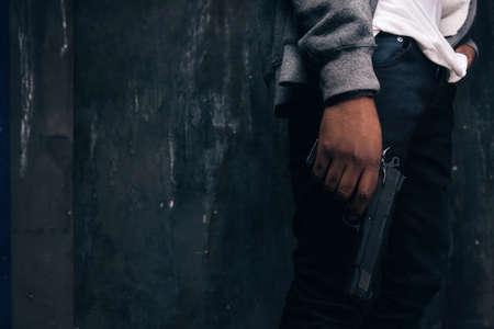 認識できない武装黒人婦女暴行者クローズ アップ スタジオ撮影。暗い背景に手で銃を持つギャングの男。アウトロー、ゲットー、殺人、強盗の概念 写真素材