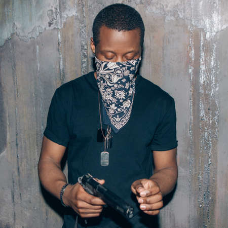 menace: Black mercenary mercenary with gun. Gangster man with weapon in hand on dark gray background. Outlaw, ghetto, murderer, armed attack concept Stock Photo