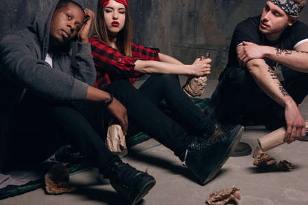 Group of homeless young people gets drunk. Youth addiction problem. Tired drunk caucasian girl holding alcohol bottle, sad and depressed guys with tattoo sits near . Social problem concept Stock Photo