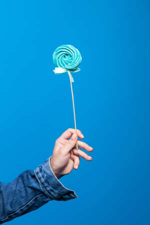 Closeup illustration of single lollipop holding in hand on blue background. Pop art of colored sweets