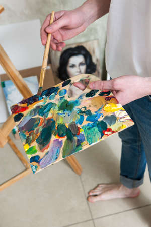 Palette with mixed colors of artist and portrait of woman on background. Painters workshop, new masterpiece, creativity and leisure concept