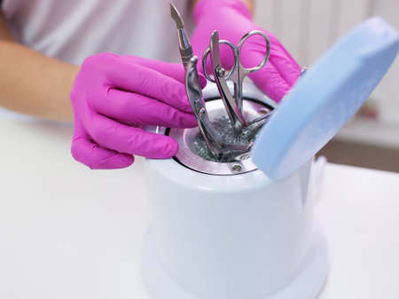 Disinfection of metal manicure tools. Salon care for beauty and health.