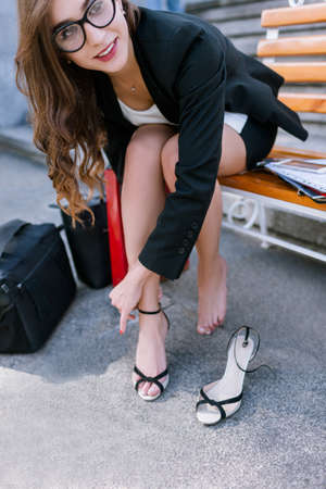 Barefoot young woman with tired legs. Confident and uninhibited girl taking off shoes, modern social behavior Stock Photo