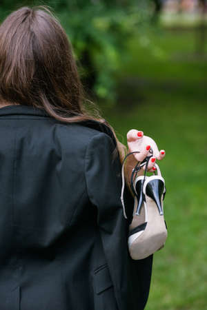 Self-confident woman walking without her shoes. Barefoot unrecognizable girl with tired legs closeup, modern social behavior