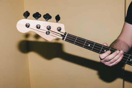 Bass guitar riff closeup. Music background. Unrecognizable guitarist playing string instrument. Band recording process