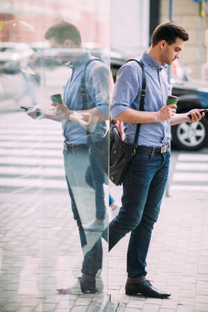 Pedestrian on coffee break on street. Young man at lunchtime, social media dependency. Technology background
