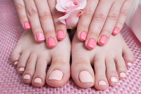 Hands with manicure, feets with pedicure. Female hands and feet on pink background top view. Result of spa salon procedure Stock Photo