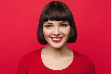 Joyful young woman openly smiling on pop red backdrop. Happiness background. Good news for pretty girl, lively face, fortune concept