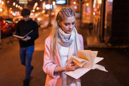 bookworm: Bookworm on night street. Interesting reading. Student studying outside, search for information in textbook