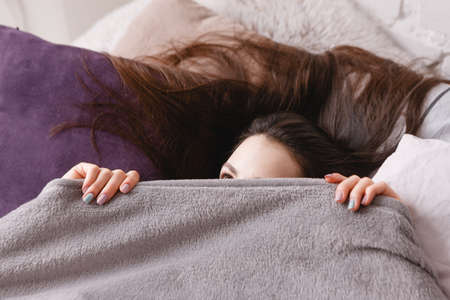 Morning hide-and-seek. Young sleepy-head woman waking up. Stock Photo - 85330654
