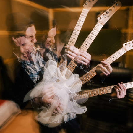 Aggressive heavy music. Male guitarist portrait. Creative recording studio, split personality, dark psychological condition with drugs