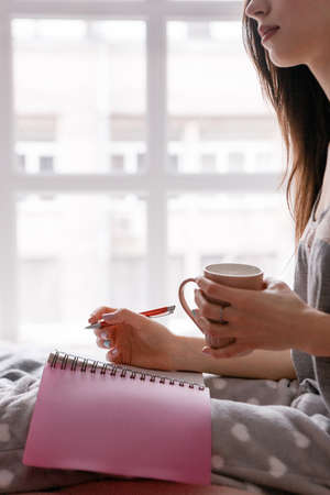 Young woman with cup of tea makes notes in writing book. Good morning with favorite drink and diary, memories and thoughts, to-do list for day, side view close up