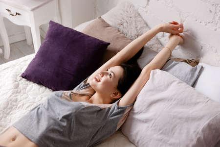 Mujer joven que estira los brazos debajo de los rayos de sol. Los sueños del pasado en la mañana, la calma y la relajación, permanecer en la cama por un tiempo en el concepto de vacaciones