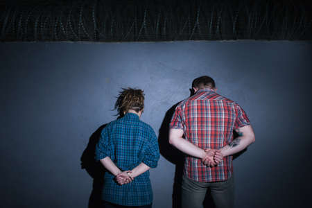 형사 커플. 범죄 동료. 파란색 배경에 감금 된 인식 할 수없는 사람들, 밤에 청소년을 체포, 등 뒤에있는 손, 유죄의 개념 스톡 콘텐츠
