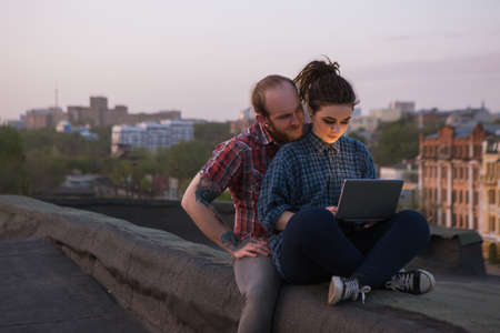electronic background: Busy working female. Couple distraction. Modern hipsters on roof, social media activity outdoors. Freelance with laptop, urban background