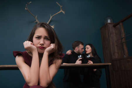 Cheating relationships. Unhappy betrayed girl. Love affair behind back, male cheater with friend. Unfaithful partner, pretty female with horns on blue background in focus on foreground Stock Photo