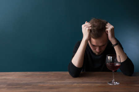Despondent drunk young man in bar. Sad thoughtful male on blue background with free space, troubles in life with red wine. Unlucky date, bad habits, breakup Stock Photo
