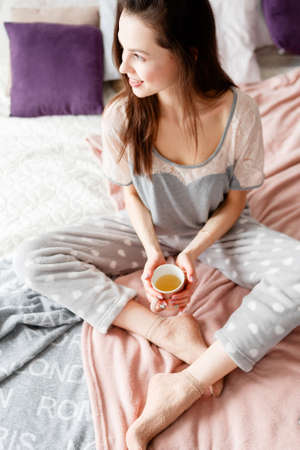 tenderly: Smiling young woman sits in bed and tenderly holds cup of tea. Enjoyment and calmness, relaxation and good mood concept. Positive start of the day, top view
