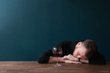 Drunk young male sleeping in bar. Unlucky date. Problems in adult ife, tired man with red wine on blue background with free space. Bad day, trouble in business concept