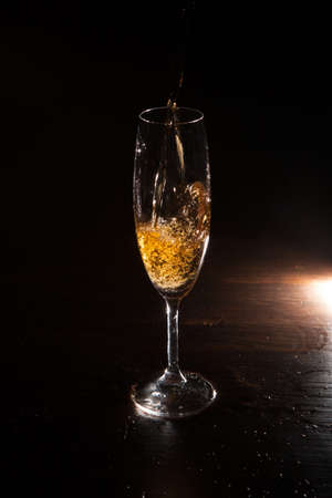 Champagne splash in motion on black background. Alcohol advertising closeup, exquisite beverage pouring in champagne flute. Tasty alcoholic drink, commercial concept