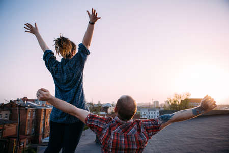 Freedom life. Happy free couple on roof. Unrecognizable hipsters watching sunset. Relief from problems, urban background with free space Stock Photo