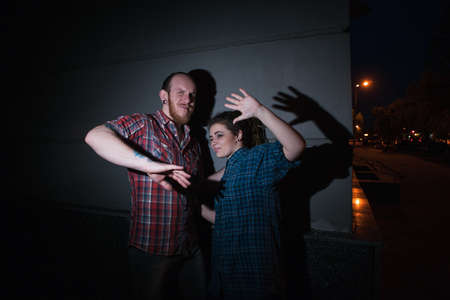 Caught hipster criminals. Forbidden relationships. Young couple on night street, adultery, bright light on dark background, detained offenders, crime concept Stock Photo - 87245815