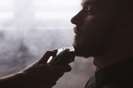 salon background: Shaving stylish man closeup. Barbershop backdrop. Fashionable male in focus on foreground, atmospheric place with white smoke, unrecognizable woman with electric razor