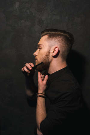 salon background: Neat hipster male combs his beard. Modern stylish man closeup on dark background, youth portrait, beauty concept Stock Photo